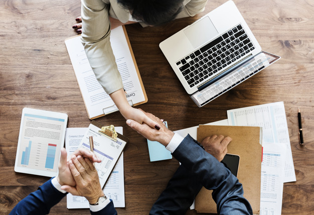 laptop on desk with paper work and business people shaking hands